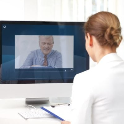 Portrait of financial assistant sitting at her workplace in front of computer and having video chat with executive businessman.