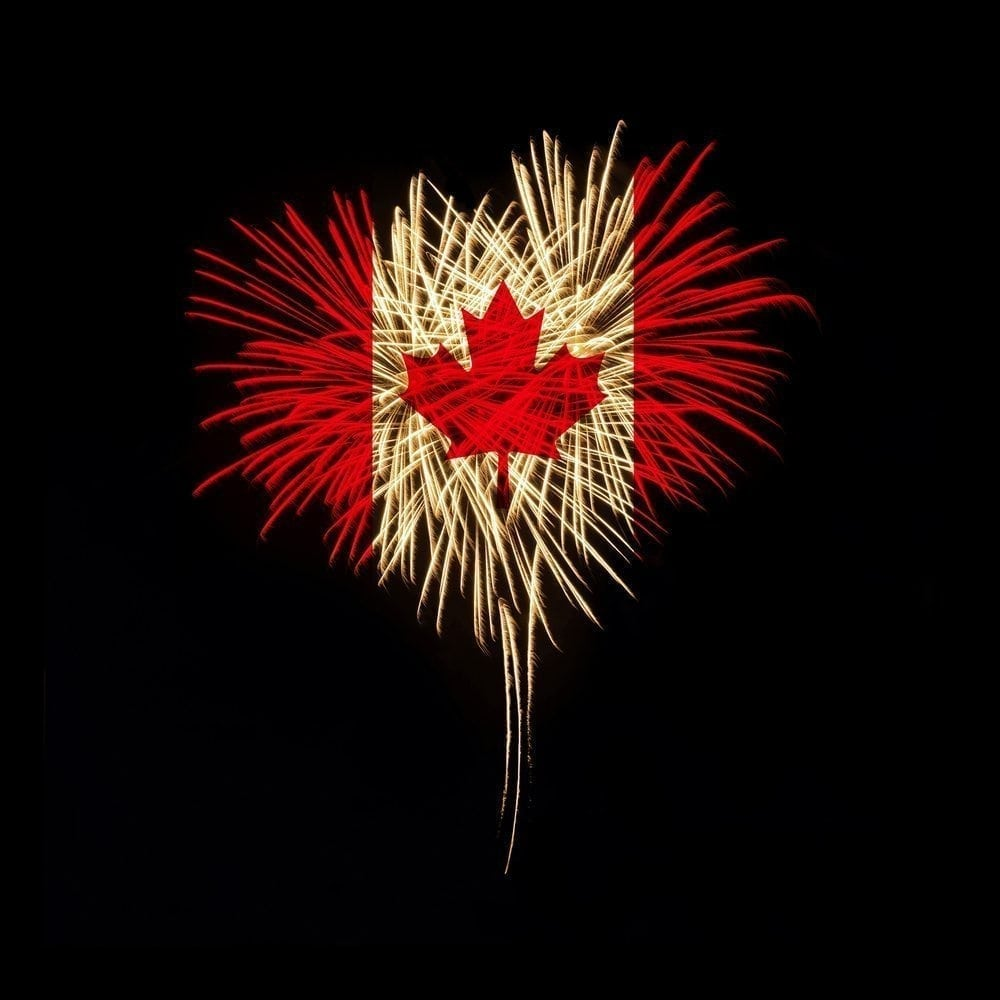 Fireworks in a heart shape with the Canada flag on a black background.